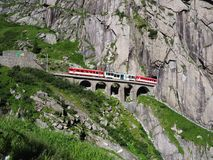 Red express train on scenic stony St. Gotthard railway bridge and tunnel, swiss Alps, SWITZERLAND. Express St. Gotthard train on Teufelsbruecke, Devil`s railway Stock Photos