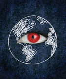 Red eye over blue texture surrounded by a drawing of the earth Stock Photo