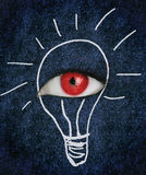 Red eye over blue texture surrounded by a drawing of a lightbulb Royalty Free Stock Photo