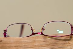 Red eyeglass on aged , orange book page close up macro shot. Copy space royalty free stock photo