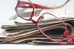 Red eyeglass on a stack of folded newspaper. Royalty Free Stock Image