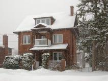 red för häftig snöstormtegelstenhus Arkivfoto