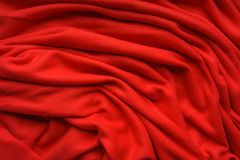 Red fabric fleece, wave, draperies. Beautiful textile backdrop. Close-up. Top view Stock Photo