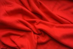 Red fabric fleece, wave, draperies. Beautiful textile backdrop. Close-up. Top view Royalty Free Stock Images