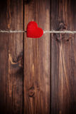 Red fabric heart hanging on clothesline Stock Photos