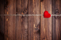 Red fabric heart hanging on clothesline Royalty Free Stock Images