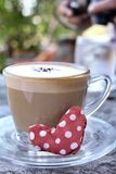Red fabric heart with hot cappuccino Stock Image