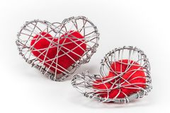 Red fabric heart in knitted wire cage Stock Photos