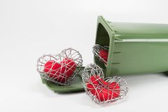 Red fabric heart in knitted wire cage on white background Stock Image