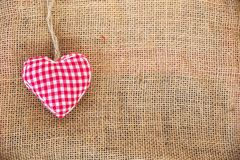 Red fabric heart, rustic canvas background. Red fabric heart on rustic canvas background royalty free stock photography