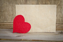 Red fabric heart with sheet of paper on a wooden board Royalty Free Stock Image