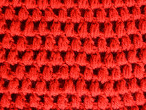 Red Fabric texture puff crochet stitches. Red crocheted yarn textured fabric with puff stitches technique Stock Photo