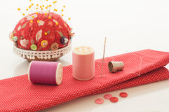 Red fabric, thread and other sewing tools. Royalty Free Stock Images