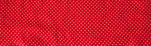 Red fabric with the white polka dots as a background texture composition.  stock photography