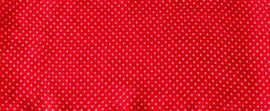 Red fabric with the white polka dots as a background texture composition.  stock images