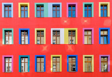 Red facade with colourful windows Royalty Free Stock Photos