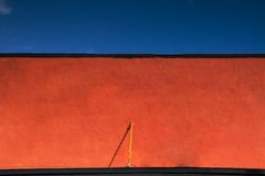 Red Facade Top. Top of a red stucco facade with blue sky above Royalty Free Stock Photos