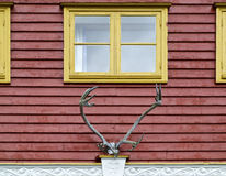 Red Facade with Yellow Windows. Facade of a red wooden house with yellow windows and a reindeer antlers as a decoration Royalty Free Stock Photo