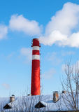 Red factory chimney against blue sky Stock Images