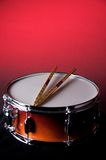 Red Fade Snare Drum and Sticks. Red fade snare drum withe gold drum sticks isolated against a red background in the vertical or portrait view Royalty Free Stock Photos