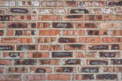 Red faded burned old bricks background with flaws and splits. On it surface royalty free stock photo
