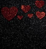 Red shiny faded hearts on a black background. Red faded Valentine`s day hearts with bright white spots on a black glittery background stock photo