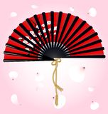 Red fan and petals. Against flying petals large red-black fan with a picture of the cherry blossoms Royalty Free Stock Photo