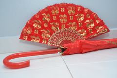 A red fan and umbrella used in traditional asian chinese weddings. The red fan and umbrella used by the bride during Asian Chinese weddings. The bride will need royalty free stock image