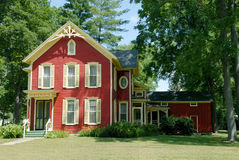 Red Farm House. An old farmhouse in the country with red siding and cream colored shutters and gingerbread trim sits in the shade of huge trees Royalty Free Stock Images