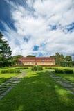 Red farm house in a garden Royalty Free Stock Photos