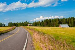 Red farm with the road, blue sky and green field Stock Photo
