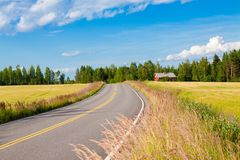 Red farm with the road, blue sky and green field Royalty Free Stock Image