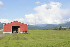 Red Farm Shed and Field. Farm equipment is parked in a shed in anticipating a successful season Royalty Free Stock Photo