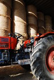 Red farm tractor. Closeup of a red farm tractor with round bales of hay/straw in the background royalty free stock photos