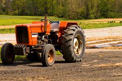 Red farm tractor in field