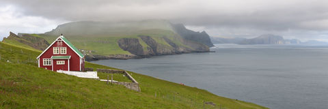 Red farmhouse on coast of Mykines Stock Photos