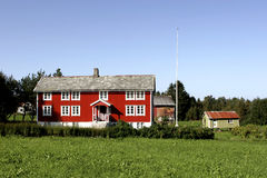 Red farmhouse in countryside. Scenic view of red farmhouse building in countryside with barn, Norway stock photo