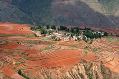 Red farmland with village in dongchuan of china Royalty Free Stock Photography