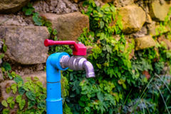 Red faucet, blue plastics pipe Stock Images