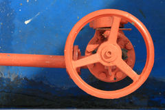 Red faucet wheel. Red rusty industrial faucet wheel on blue background Stock Image