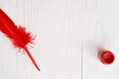 Red feather and ink. On white background Royalty Free Stock Image