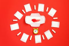 Red feather lies on sanitary pads and tampons near the alarm clock on red background. stock images