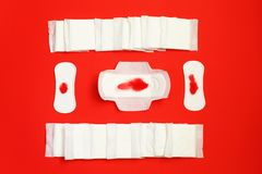 Red feather and sanitary pads and absorbent sheets on red background. Sanitary pads and absorbent sheets on red background. Menstrual pad and tampon. Woman stock image