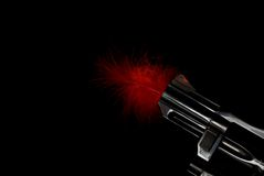 Red Feathered Gun Barrel. Short revolver barrel with red feather sticking out, black iso Stock Image