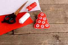 Red felt Christmas tree decor, scissors, red and white felt sheets, thread, needle on wooden background with empty space for text Royalty Free Stock Image