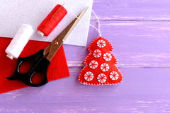 Red felt Christmas tree ornament, scissors, red and white felt sheets, thread, needle lilac on wooden background with blank space. Home decor. Crafts idea for Royalty Free Stock Images
