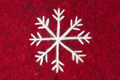 Red felt with embroidered white snowflake Royalty Free Stock Photography