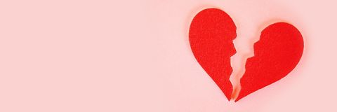 Red felt heart broken into two halves on a pink background.  stock photos