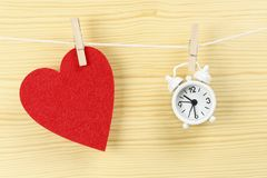 Time for love. Red felt heart and clock on clothesline, time for love concept Stock Photos