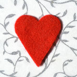 Red felt heart on decorative background Stock Photos